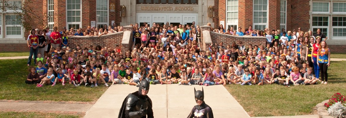 Entire school in front of our building with Batman and Batgirl.
